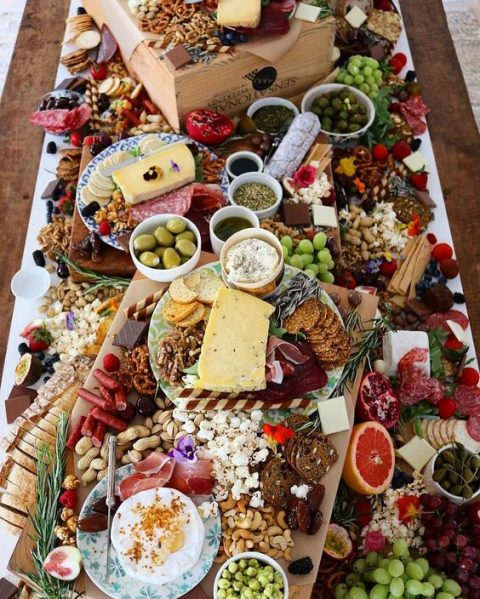 a charcuterie table with lots of types of nuts, vegetables, cheese, salami, crackers and grapes