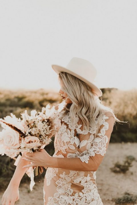a chic boho lace wedding gown styled with a creamy fedora hat