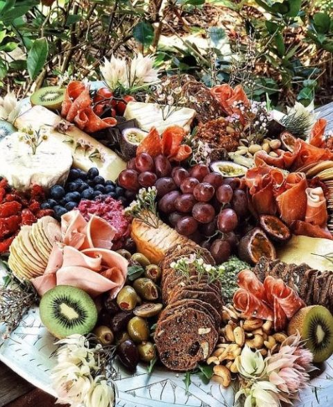 a chic charcuterie board with crackers, fruits, vegetables and various types of jamon and prosciutto