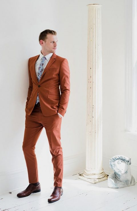 a chic rust-colored suit with a white shirt and a floral tie