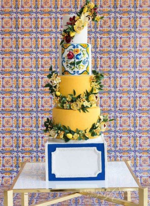 a colorful Mediterranean wedding cake with yellow and a white tier and a colorful tile tier