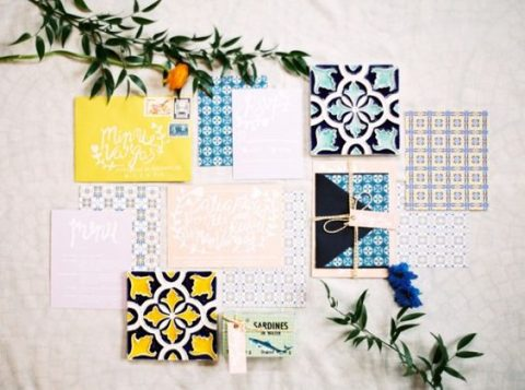a colorful wedding invitation suite done in yellow, blue and white with azulejo tiles