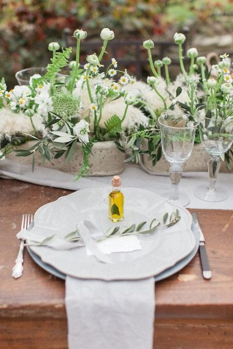 a cozy Mediterranean reception table with neutral textiles and porcelain, potted plants and blooms, pampas grass