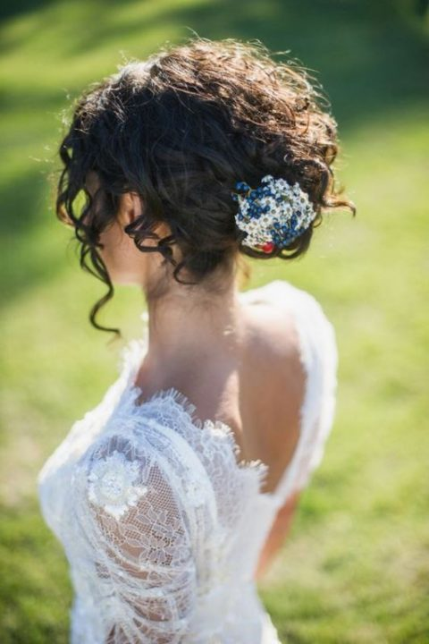 a curly updo with a bead and sequin hairpiece and some bangs