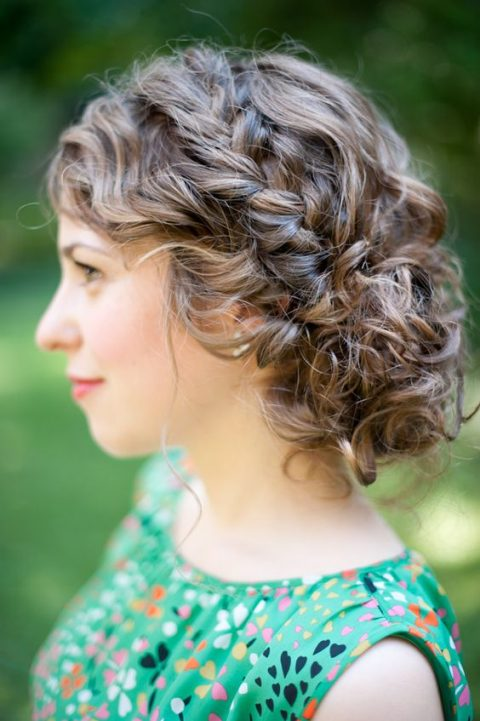 a curly updo with a side braid for a rustic or boho bride