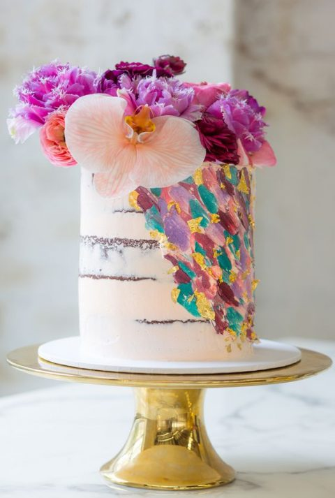 a fantastic handpainted wedding cake with colorful brushstrokes and bold fresh blooms on top
