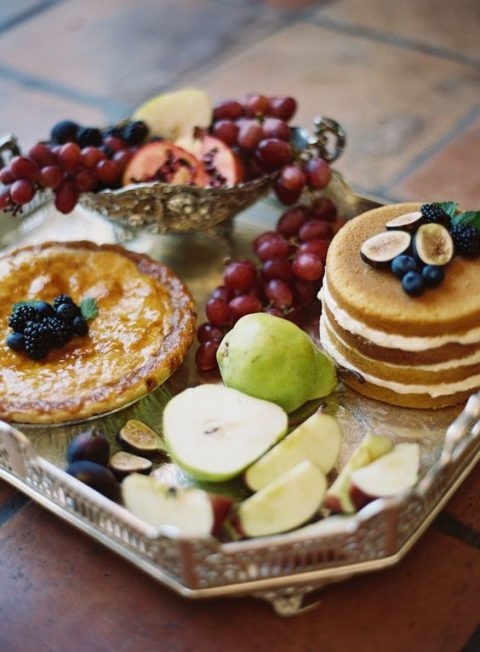 a fruit board and some traditional desserts served on a vintage silver tray