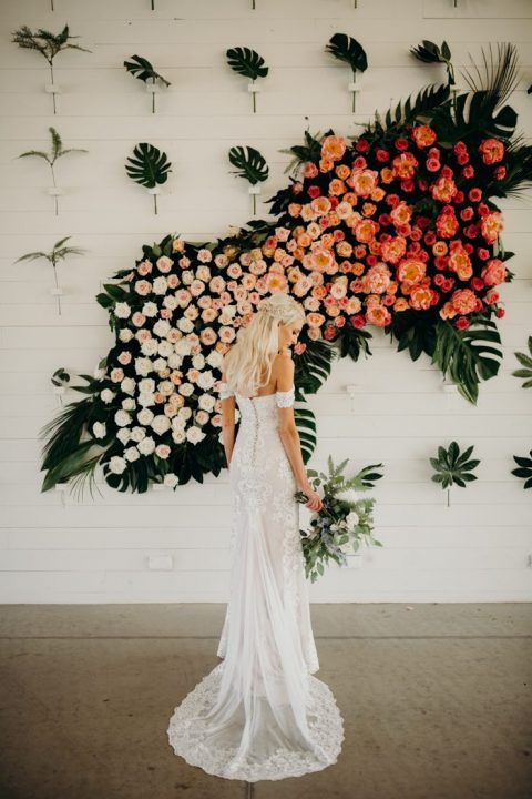 a gorgeous wedding backdrop done of tropical leaves and lush ombre florals from white to bold pink