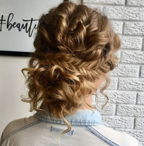 a loose curly updo with a fishtail braid is a great idea for a boho bride