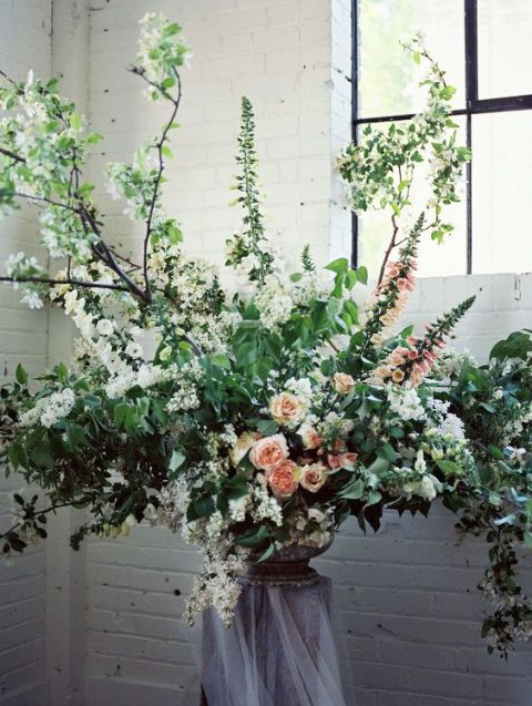 a lush floral decoration of lots of greenery and white and blush blooms