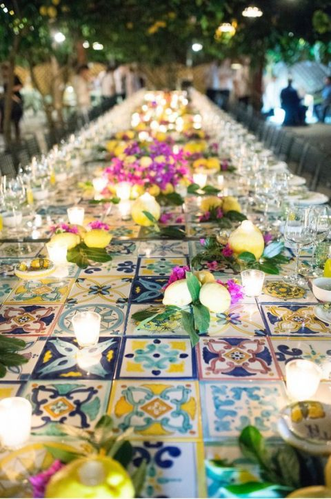 a reception tabble fully clad with colorful azulejo tiles, with lemons and candles