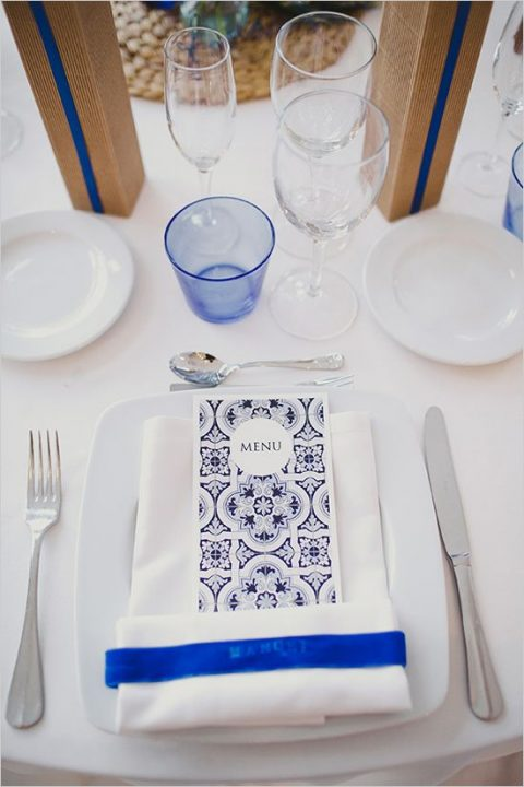 a reception table done with bright blue touches and an azulejo-styled menu