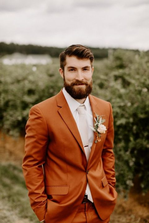 a rust-colored groom_s suit with a white shirt and a creamy tie