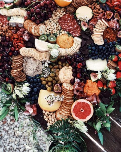 an epic grazing table with lots of fruits, nuts, cheese and salami