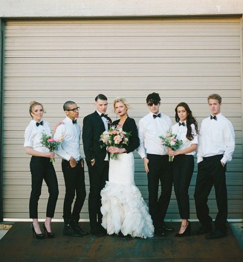both bridesmaids or groomsladies and groomsmen wearing white shirts, black pants and bow ties and black shoes