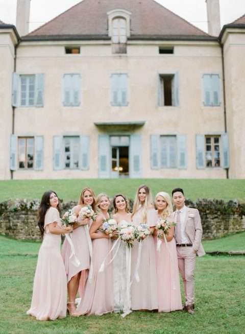 bridesmaids wearing pink dresses and a bridesman rocking a pink suit with a tie and a white shirt