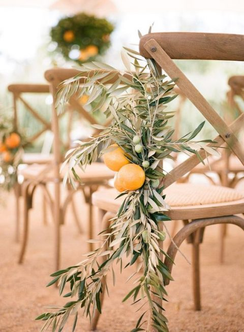 decorate your aisle chairs with olive branches and fresh citrus to give it an aroma and a Mediterranean feel
