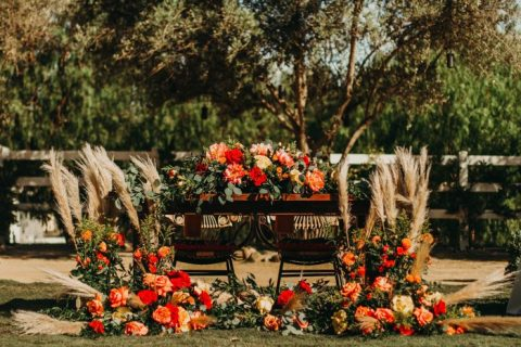 fantastic sweetheart table decor done with pampas grass, bold orange and red blooms and greenery