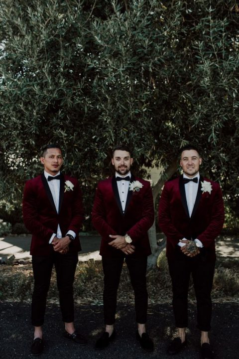 fashionable groomsmen style with black cropped pants, black moccasins and burgundy velvet tuxedos