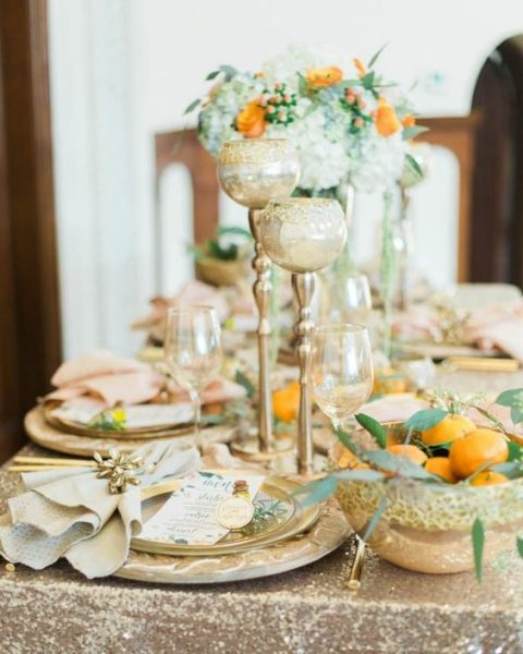 glitter, metallic touches and citrus with greenery for a warm-colored table setting