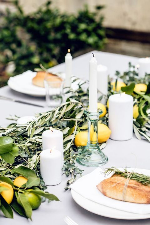 simple table styling with olive branches, lemons and limes plus white candles feel very Mediterranean-like
