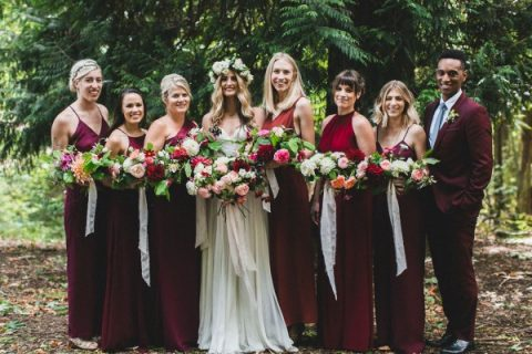 the bridesmaids and bridesman all wearing plum-colored attire