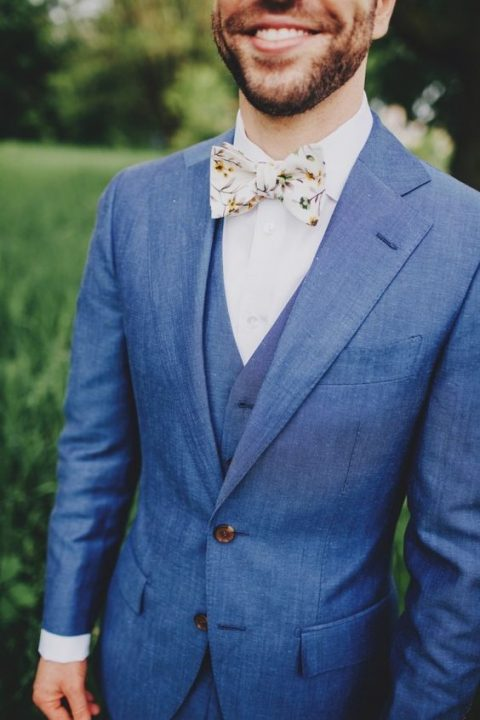 a blue three-piece suit and a whimsy floral bow tie