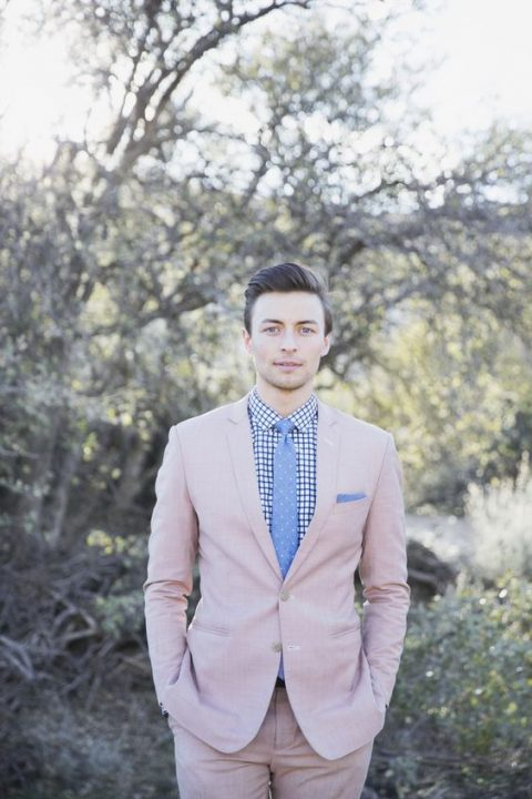 a blush suit, a printed shirt and a blue polka dot tie
