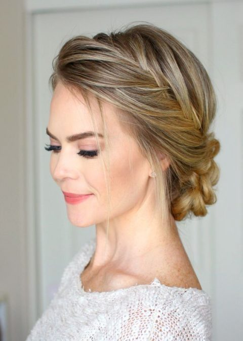 a braided side halo with a braided low bun and some locks down