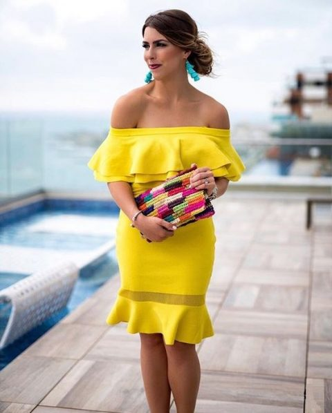 a bright yellow off the shoulder ruffle dress, turquoise earrings and a colorful clutch