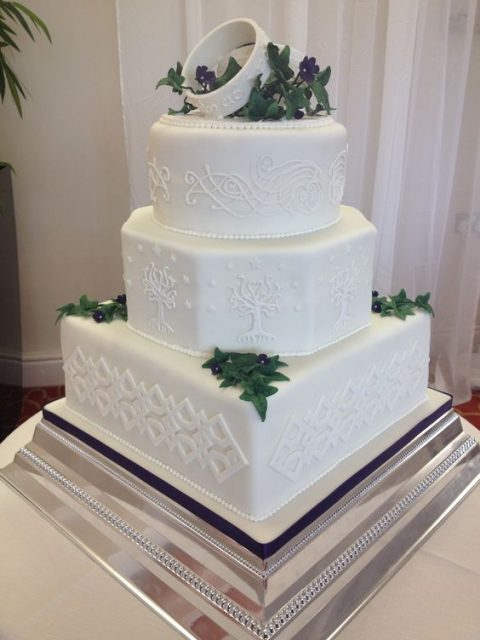 a buttercream wedding cake with rings on top, edible greenery and leaves and textural images