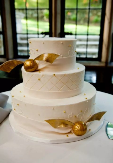 a chic wedding cake in white with gold beads and Golden Snitches