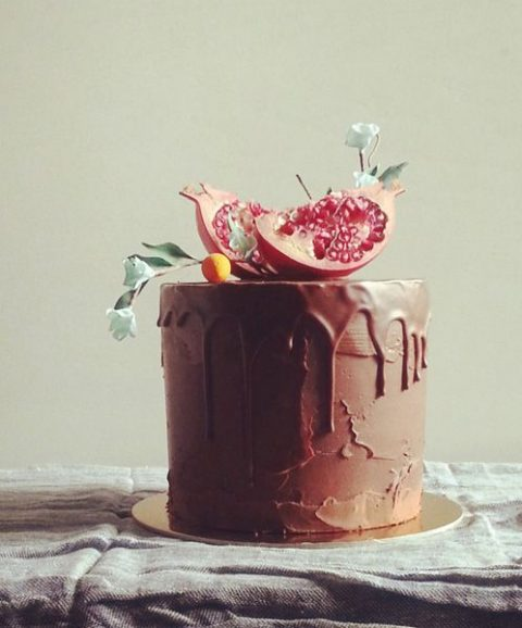a chocolate ganache wedding cake with blooming kumquat branches and fresh pomegranates