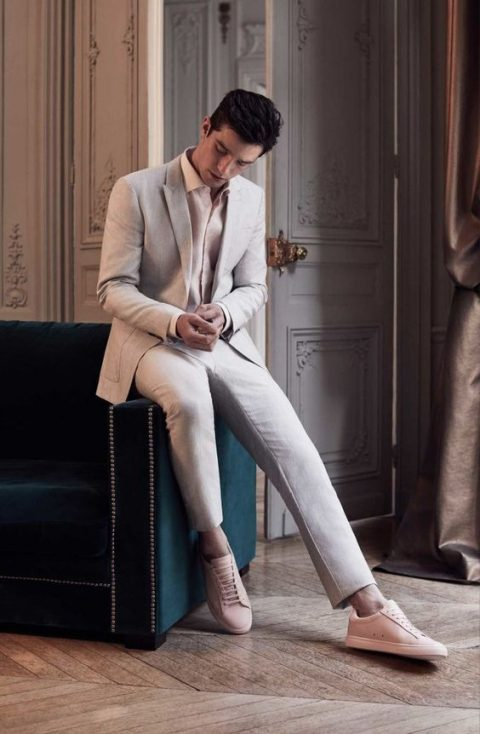 a cremay suit, a blush shirt and blush sneakers for a relaxed groom_s look