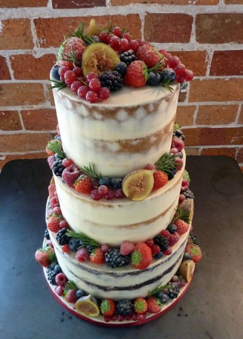 a delicious semi naked vegan wedding cake decorated with fresh fruit including figs, blackberries, blueberries, strawberries and others