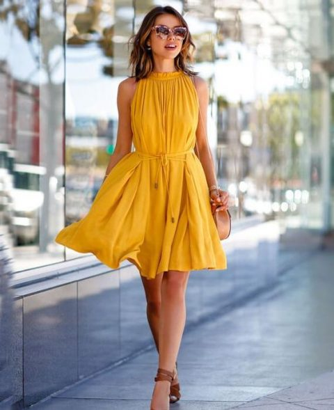 a flowy sleeveless yellow knee dress with drapings, ties and brown shoes
