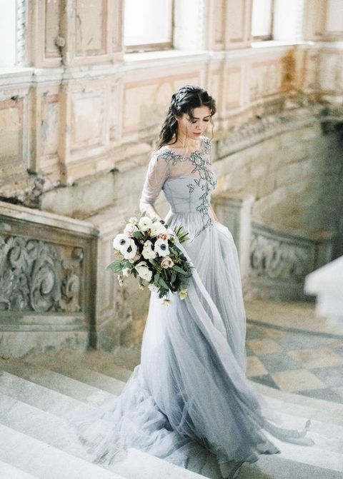 a grey blue wedding dress with an embroidered bodice, long sleeves and a layered skirt
