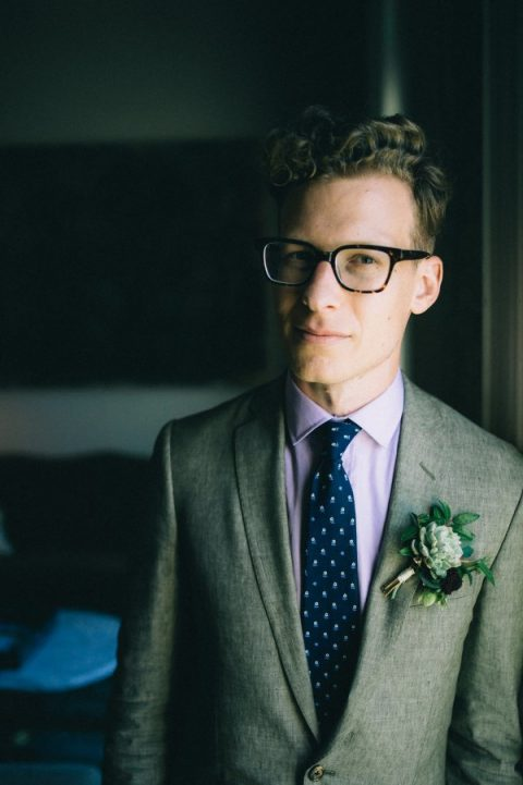 a grey suit, a lilac shirt and a navy printed tie plus a succulent boutonniere