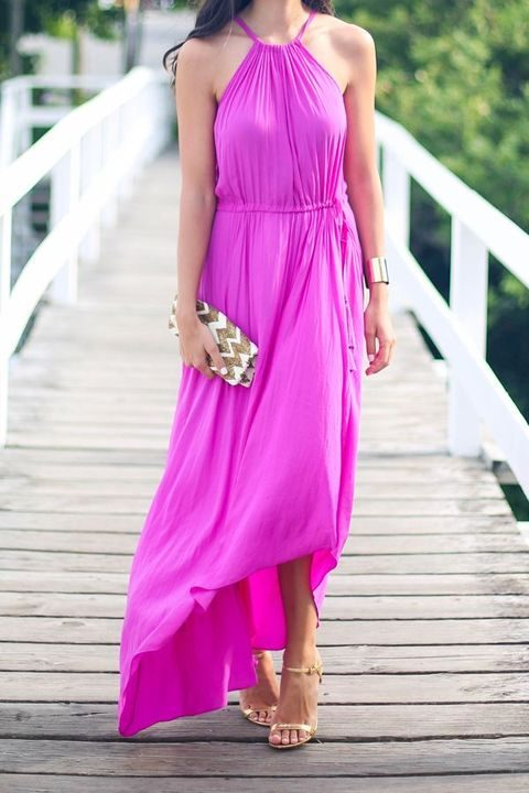 a hot pink maxi dress with an asymmetrical skirt and a halter neckline, a metallic bracelet and shoes