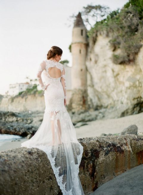 a lace fitting wedding dress with a cutout back and a sheer skirt with a train