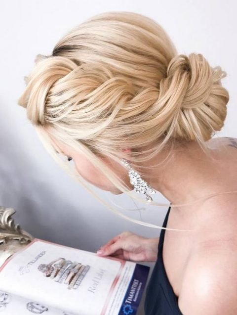 a large sided braided updo with a low bun and some locks down