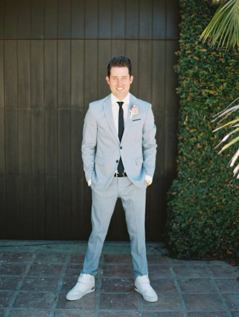 a light blue suit, a white shirt and a black tie plus neutral sneakers