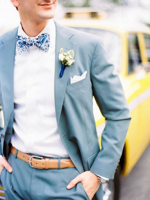 a light blue suit with a white shirt and a whimsy printed bow tie