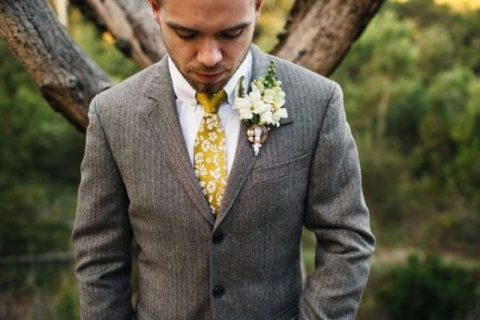 a light brown suit, a white shirt and a yellow floral tie