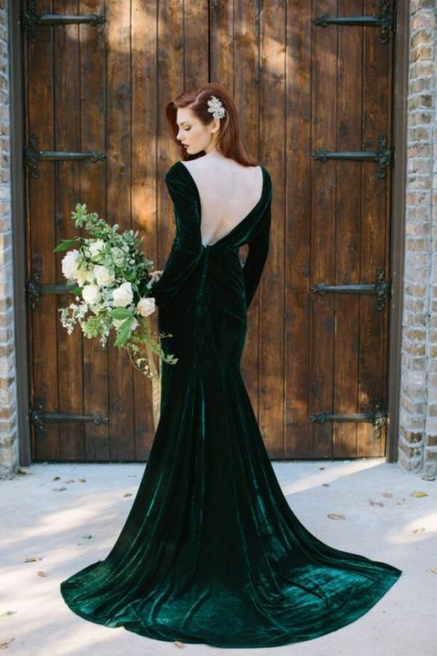 a long sleeve mermaid emerald velvet open back wedding dress with a train for a sophisticated bridal look