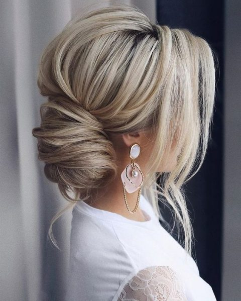 a low bun with a volume on top and some side bangs for a refined touch