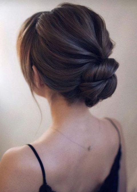 a low twisted bun with a bump on top and some bangs