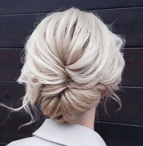 a messy low updo with a twisted braid and some locks down