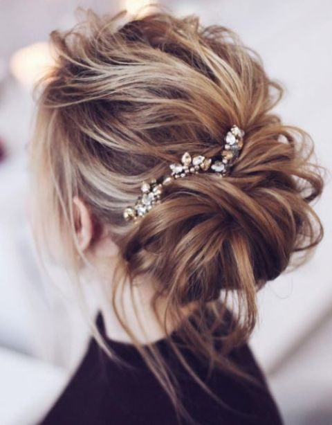 a messy updo with a rhinestone hairpiece and some locks down