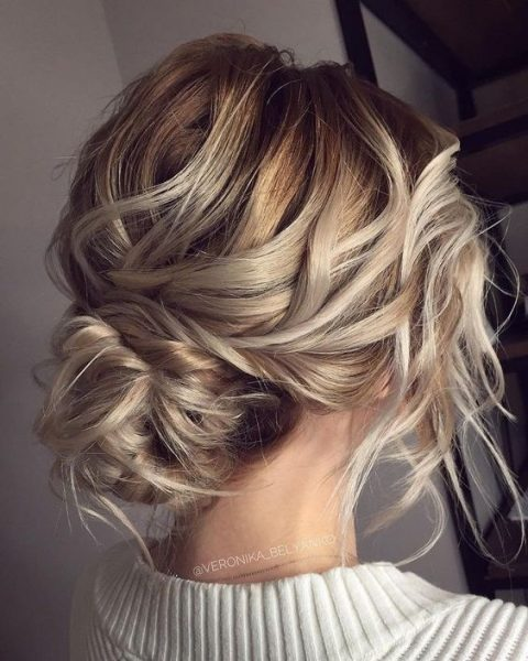 a messy wavy low bun with a bump and some waves down